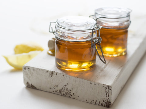 pots of honey on table with lemon