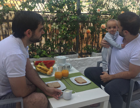 Two dads having breakfast outside with their baby boy