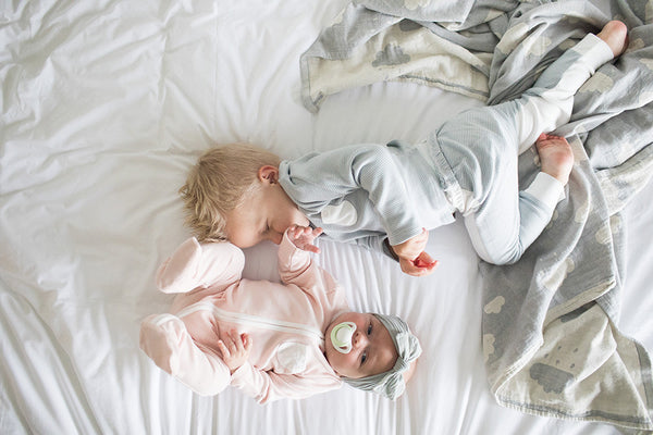 toddler brother and baby sister playing on bed together