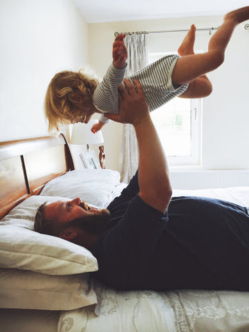 Father throwing daughter into the air like an airplane