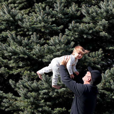 Dad holding daughter in the air outside
