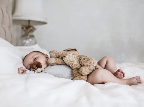 Baby with dummy and rabbit tedding sleeping in bed
