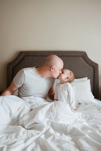 Father and little girl kissing on bed