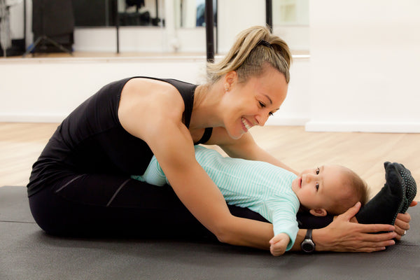 Mother with her baby doing yoga stretching