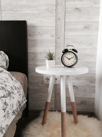 alarm clock on bedside table with plant
