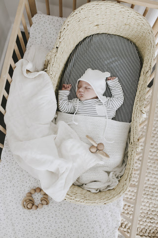 baby sleeping in moses basket in mori baby clothes
