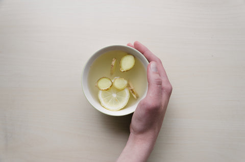 woman holding ginger and lemon in water