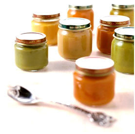 Pots of organic baby food with spoon