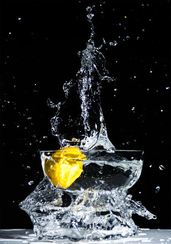lemon dropping into glass of water