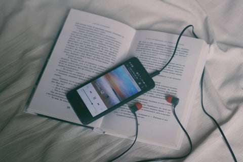 iphone and book in bed