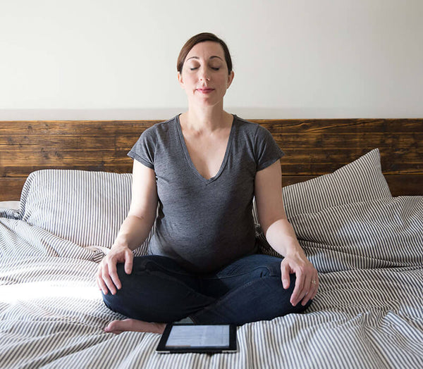 pregnant woman meditating on bed