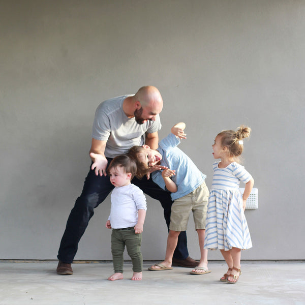 Dad with his 3 children laughing and playing