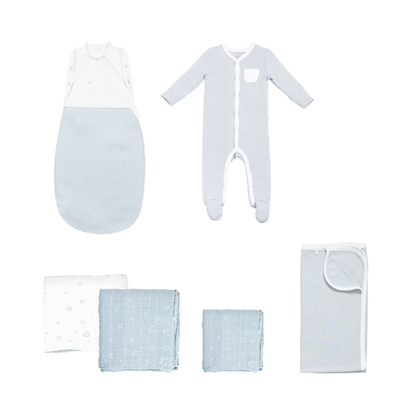swaddle set that includes a swaddle bag, two large muslins, one regular muslin, a baby blanket and a front-opening sleepsuit with feet