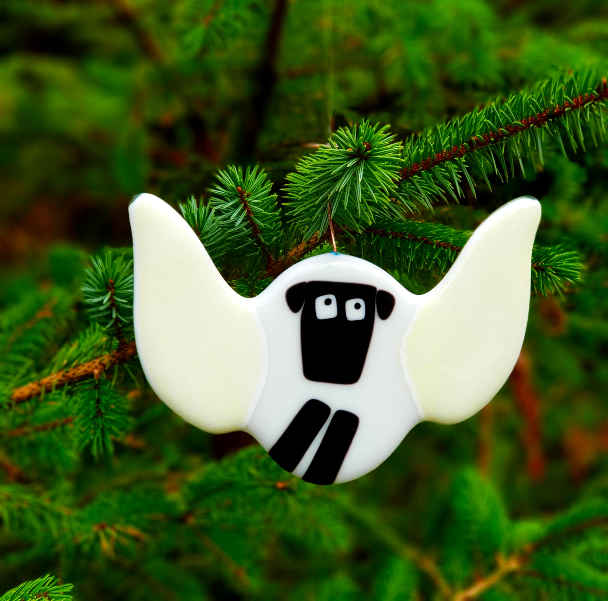 A fused glass hanging decoration featuring a sheep with angel wings