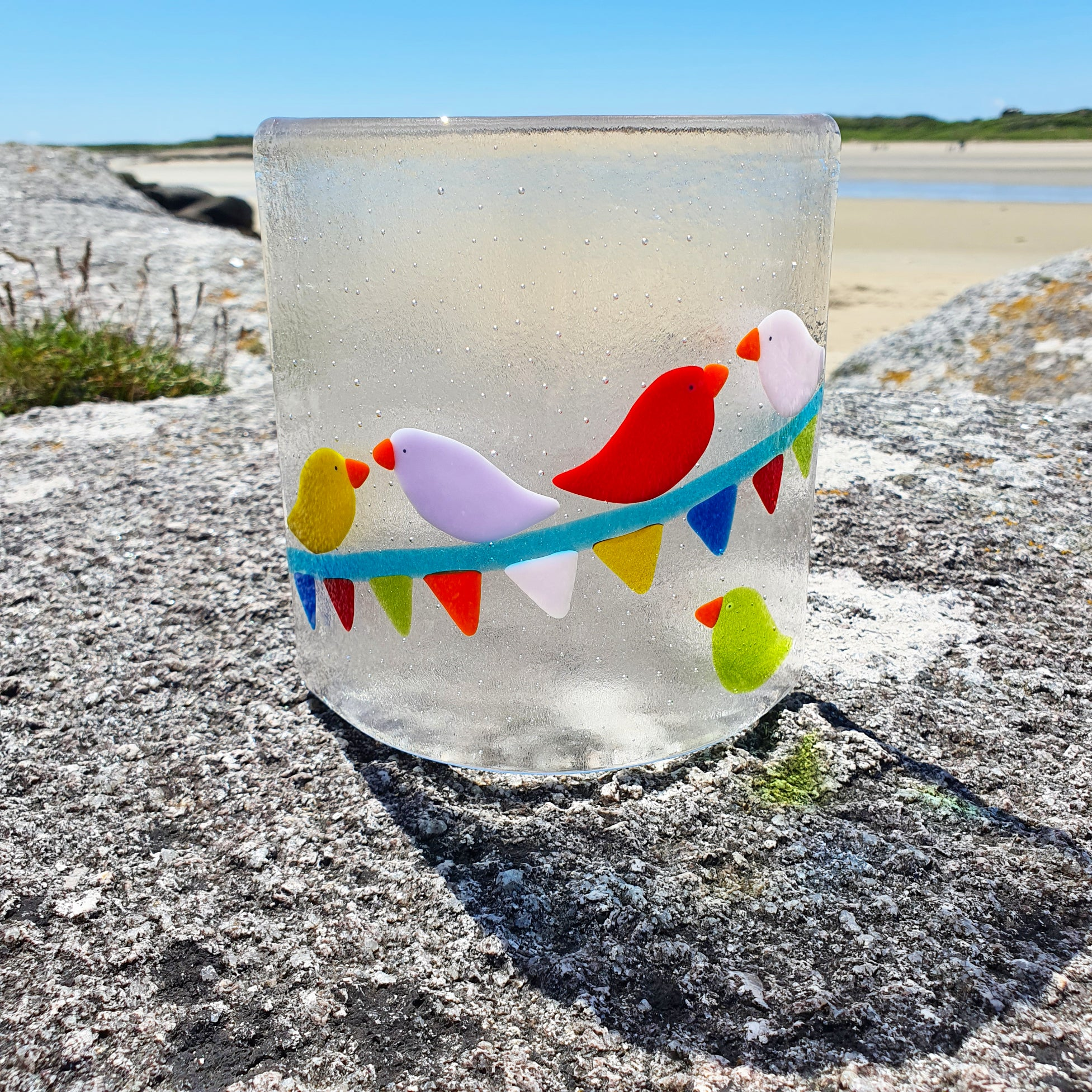 A fused glass candle shield featuring brightly coloured birds perched on carnival bunting. Made by Connemara Blue.