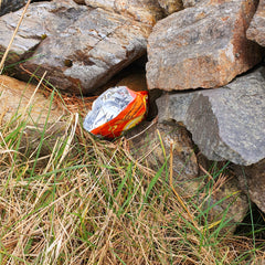 A crisp packet lodged in a stone wall, photographed on the Wild Atlantic Way by Connemara Blue