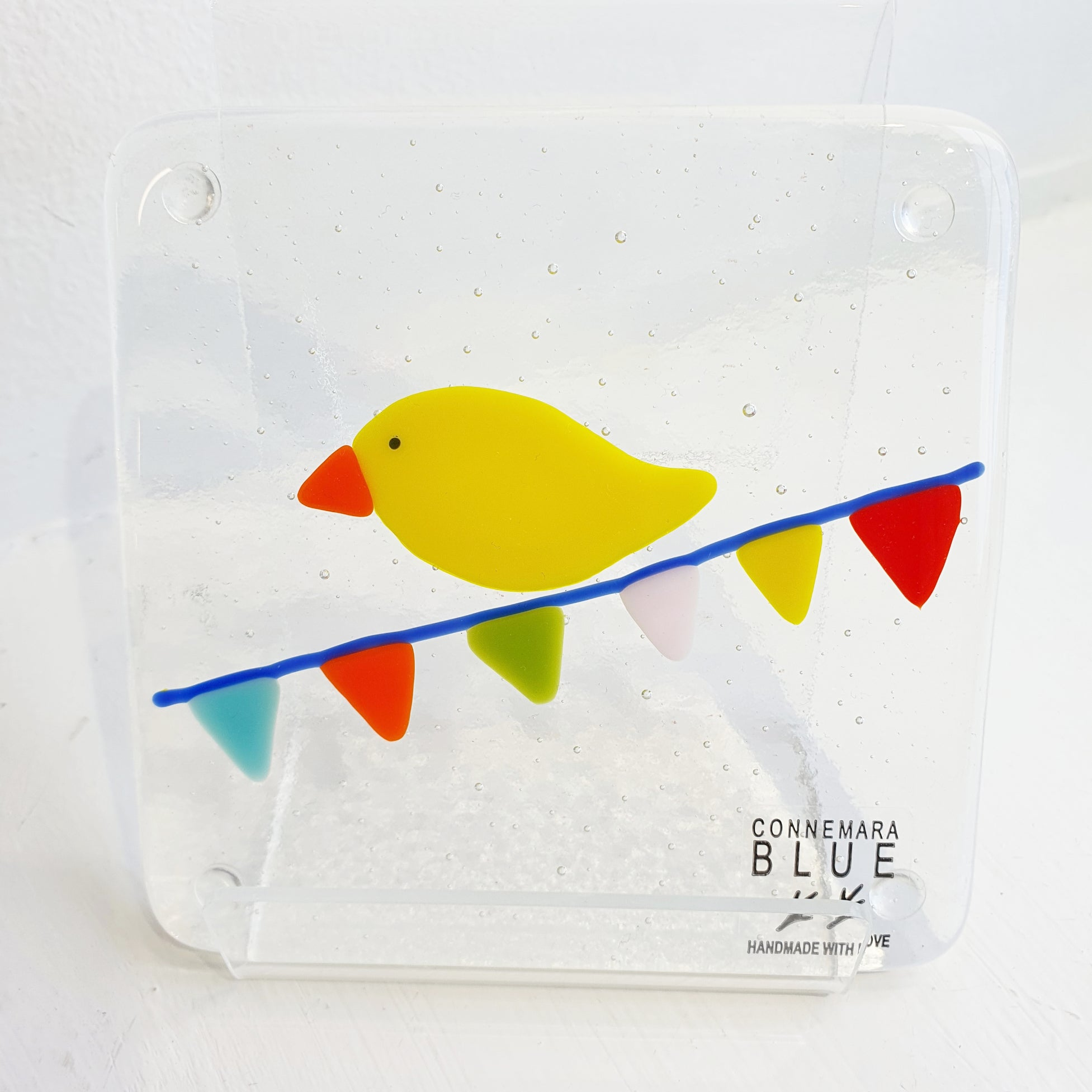 A fused glass coaster featuring a brightly-coloured bird sitting on carnival bunting. Handmade by Connemara Blue.