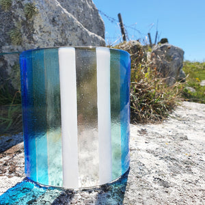 A fused glass candle shield in stripes of clear, white and blues. Hand made by Connemara Blue
