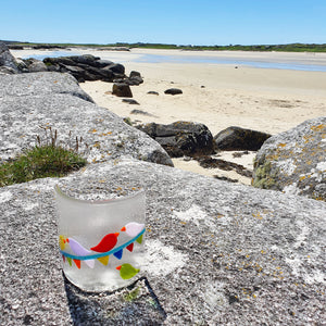 A fused glass candle shield for tea lights, featuring brightly-coloured birds sitting on carnival bunting. Handmade by Connemara Blue.