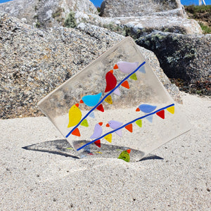 A fused glass small square plate, featuring brightly-coloured birds sitting on carnival bunting. Handmade by Connemara Blue.