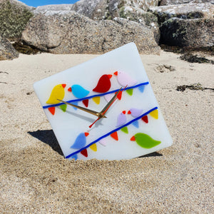 A fused glass white clock featuring brightly-coloured birds sitting on carnival bunting. Handmade by Connemara Blue.