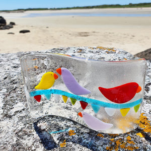 A fused glass freestanding wave sculpture, featuring brightly-coloured birds sitting on carnival bunting. Handmade by Connemara Blue.