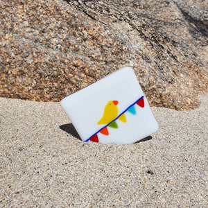 A fused white glass coaster featuring brightly-coloured birds sitting on carnival bunting. Handmade by Connemara Blue.