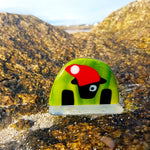 A freestanding fused glass Connemara Sheep in stripy green and wearing a Santa hat, made by Connemara Blue