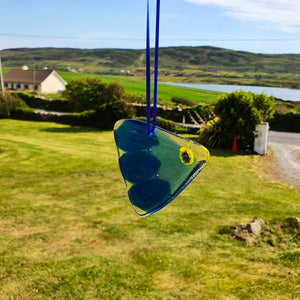 Fused glass hanging decoration in the form of a blue fish with a yellow eye, made by Connemara Blue