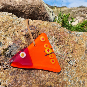 An orange fused glass hanging decoration in the shape of a fish with copper wire addition,  made by Connemara Blue