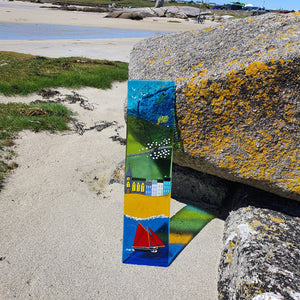 A fused glass wall panel showing a typical Connemara seaside town and a Galway hooker in the harbour.