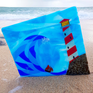 A square fused glass wall panel showing a lighthouse and Galway Hooker, made by Connemara Blue
