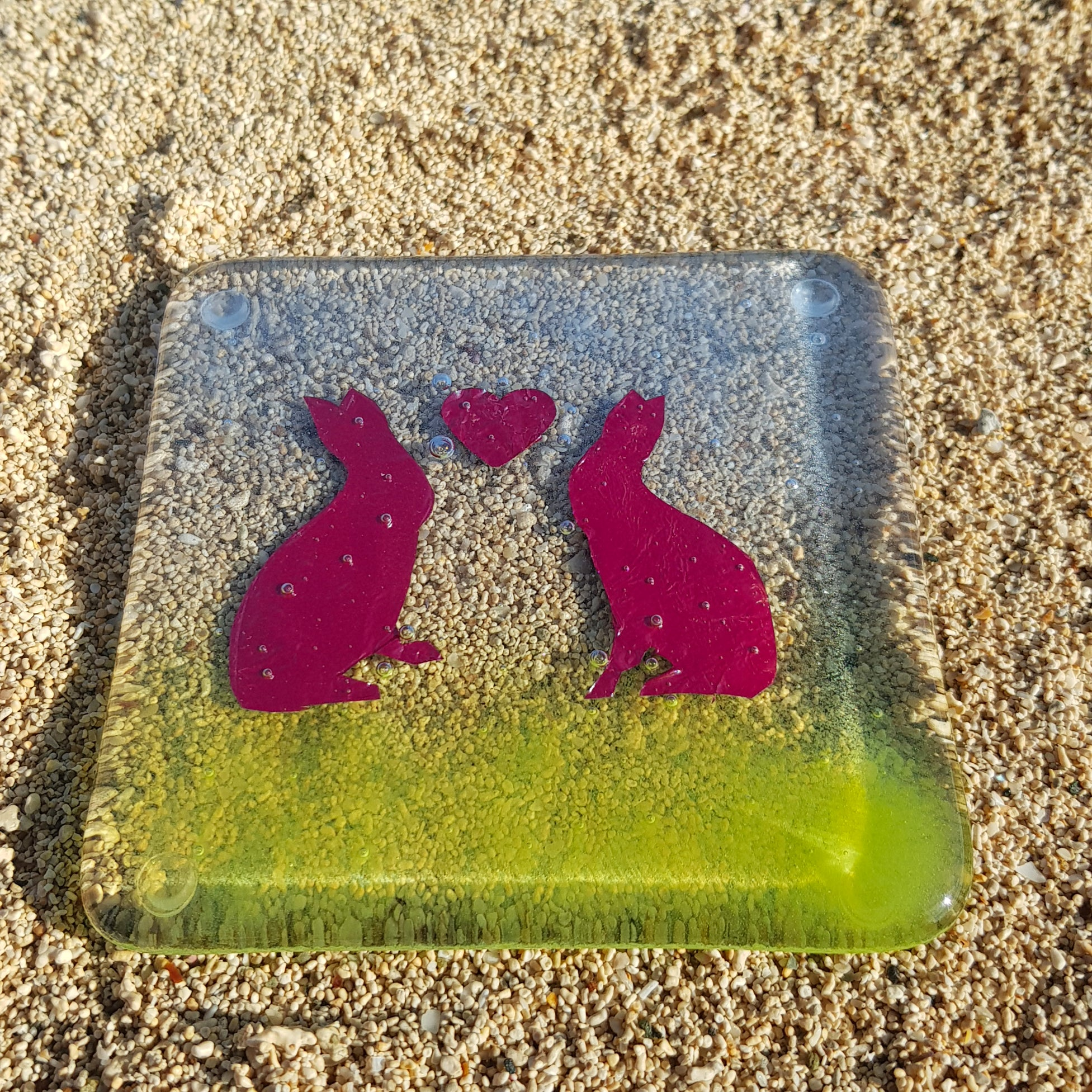 A fused glass coaster featuring two moon gazing hares, made by Connemara Blue