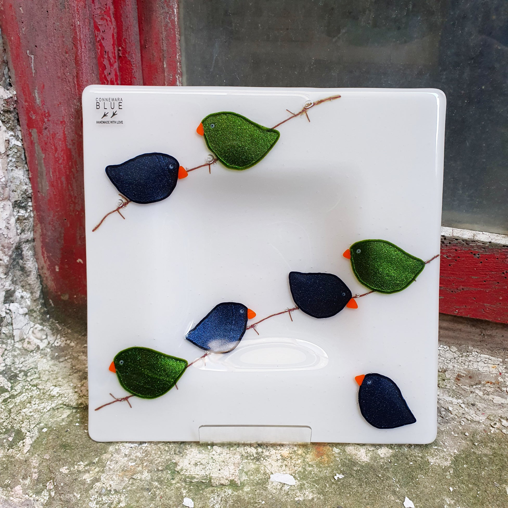A square fused glass plate featuring glittery green and dark blue birds on a wire, handmade by Connemara Blue