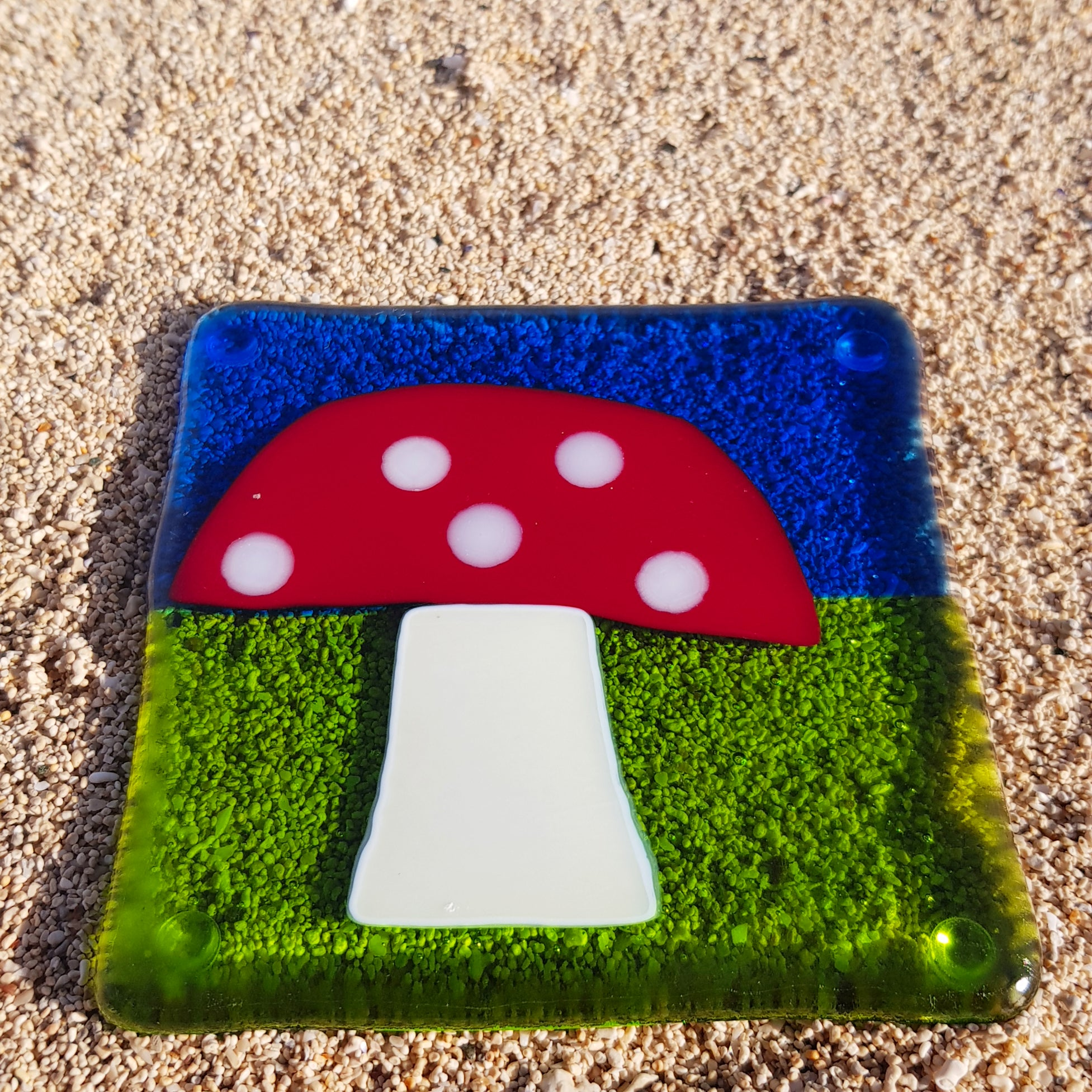 A fused glass coaster featuring a toadstool, made by Connemara Blue