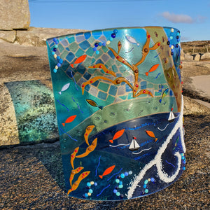 A large fused glass freestanding arch sculpture and candle shield featuring the elements of the sea: boats, fish, seaweed, pebbles, and foamy waves. Handmade by Connemara Blue