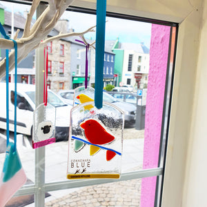 A fused glass hanging decoration featuring a brightly-coloured bird sitting on carnival bunting. Handmade by Connemara Blue.