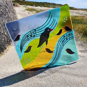 A fused glass wall panel featuring blackbirds on a wire, flocks of Connemara sheep, and a musical message,  made by Connemara Blue.