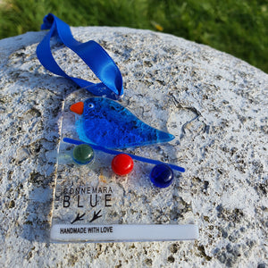 A fused glass hanging decoration featuring a bird sitting on Christmas lights, handmade by Connemara Blue