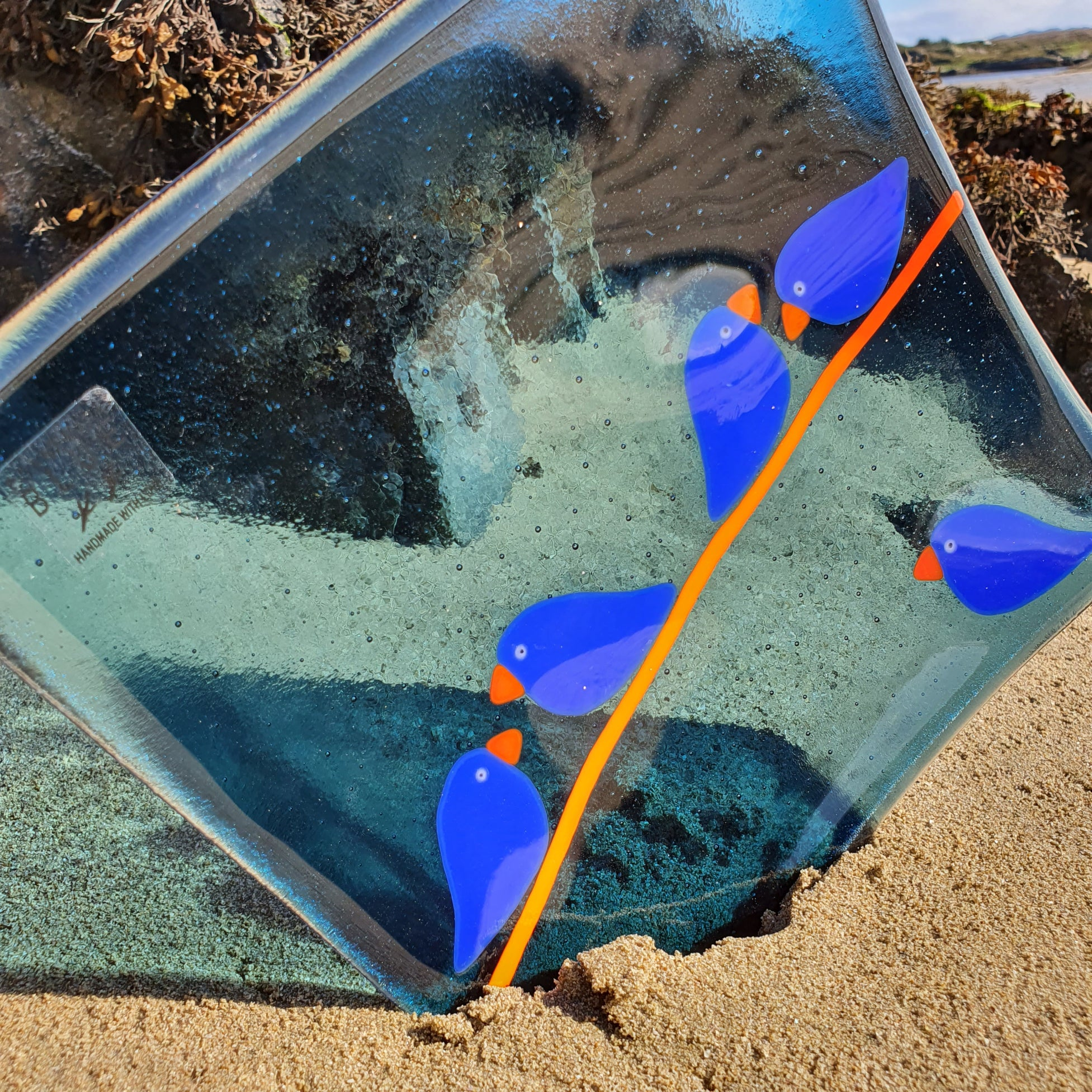 A fused glass square plate in a beautiful transparent steel blue, featuring deep cobalt blue birds on an orange wire