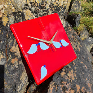 A fused glass clock featuring light blue birds perched on barbed wire, set on a vivid red background