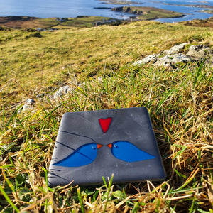 A fused glass coaster in steel blue featuring two birds and a red heart, handmade by Connemara Blue