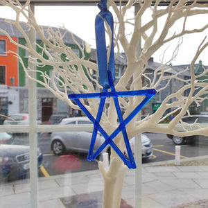 A fused glass transparent blue star decoration, handmade by Connemara Blue