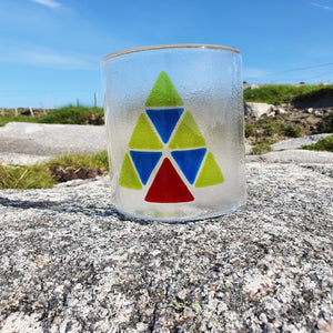 A fused glass candle shield featuring a Christmas Tree design in blue, red and green, made from hand-cut triangles.