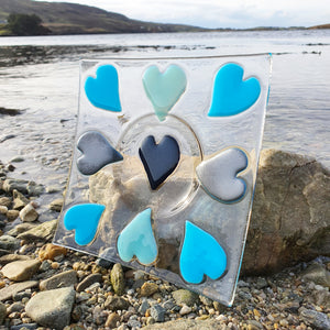 A clear glass candle or condiment holder featuring 9 hearts in different shades of blue, handmade by Connemara Blue