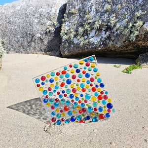 A square fused glass plate with multicoloured transparent bobbles, handmade by Connemara Blue
