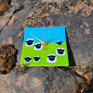 A fused glass clock featuring sheep and lambs in a field, set against a blue sky and birds