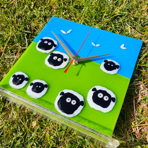A fused glass clock featuring seven Connemara sheep and lambs set against a green and blue background, handmade by Connemara Blue