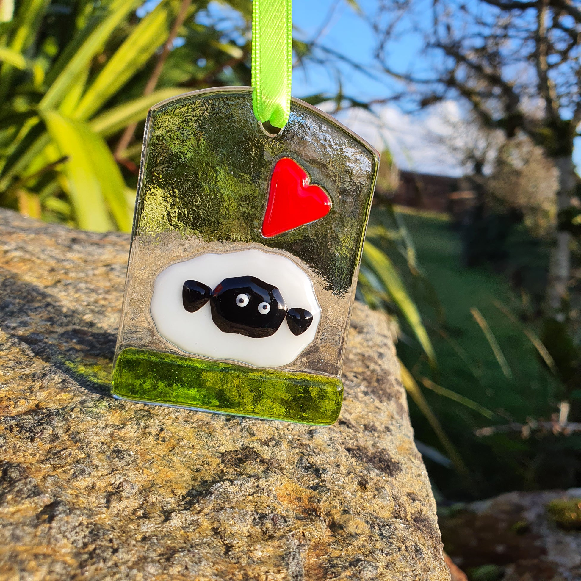 A fused glass decoration featuring a fluffy sheep and a red heart, handmade by Connemara Blue