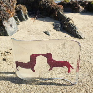A fused glass tea light shield in transparent glass, with two hand-cut copper foil dachshunds